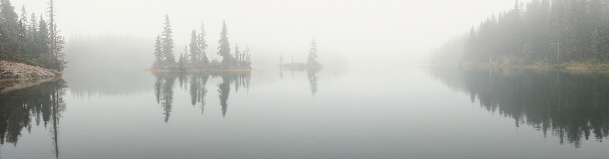Panoramic photo of a foggy lake with an island covered in evergreen trees.
